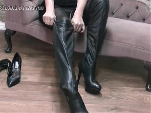 Sexy secretary babe slowly pulls on her leather thigh boots