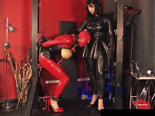 Sissy slave in latex sucks tranny